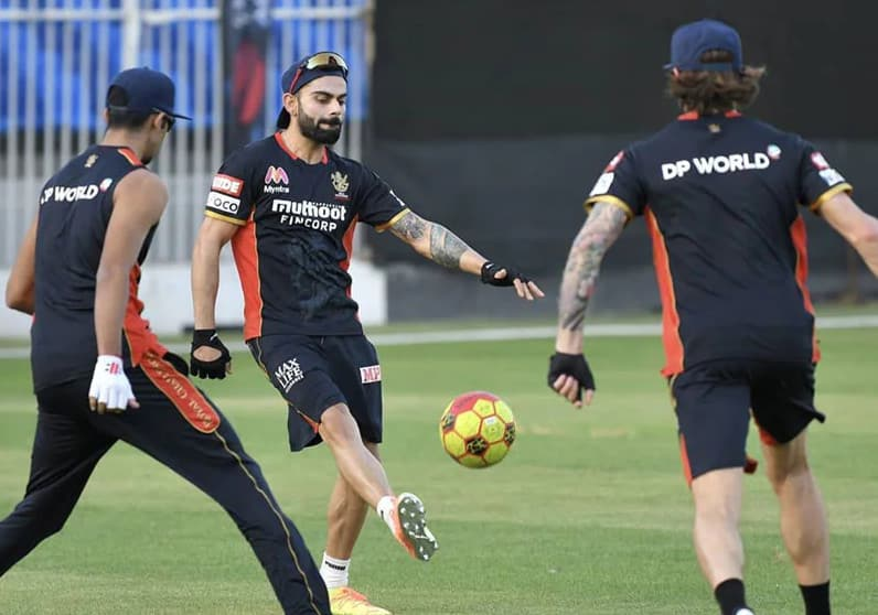 Virat Kohli plays football with his team-mates before play